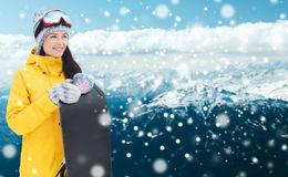 Happy young woman with snowboard over mountains Royalty Free Stock Image
