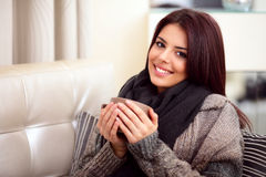 Happy young woman on sofa. Happy young woman sitting on sofa in cosy cloths with cup of coffee Royalty Free Stock Photos