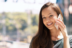 Happy young  woman speaking by cellphone indoor. Royalty Free Stock Images
