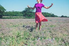 Happy young woman spinning in field of purple flowers. A happy young woman is spinning around in a field of purple flowers on a sunny summer day Stock Images
