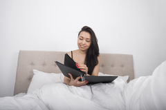Happy young woman with spiral notepad in bedroom Royalty Free Stock Photography