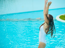 Happy young woman splashing water in pool Royalty Free Stock Images