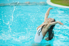 Happy young woman splashing water in pool Royalty Free Stock Photo