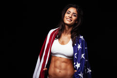 Happy young woman in sportswear holding American flag Royalty Free Stock Image