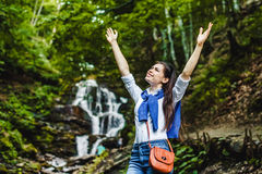 Happy young woman spreading hands enjoying nature with waterfall in background Royalty Free Stock Photo