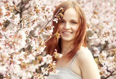 Happy young woman in spring flowers garden Stock Photo