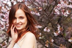 Happy young woman in spring flowers garden Stock Images