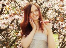 Happy young woman in spring flowers garden Royalty Free Stock Photography