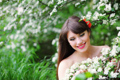 Happy young woman in a spring park smelling the flowers Stock Image
