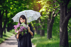 Happy young woman in a spring park with an umbrella Stock Images