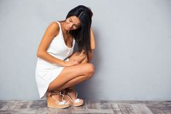 Happy young woman squatting Royalty Free Stock Image