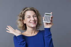Happy young woman squinting showing calculator Royalty Free Stock Images