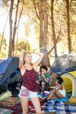 Happy young woman standing with arms raised at campsite Royalty Free Stock Images