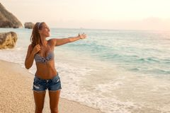 Happy young woman standing on the beach at sunset royalty free stock image