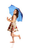 Happy young woman standing with a blue umbrella. Isolated Royalty Free Stock Images