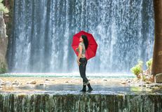 Happy young woman standing in a creek with a red umbrella in front of an impressive water fall stock images