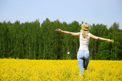 Happy young woman is standing on a field Stock Image
