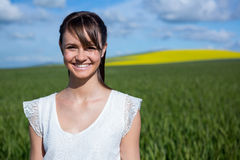 Happy young woman standing in field Stock Photos