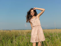 Happy, young woman standing in green field Stock Photo