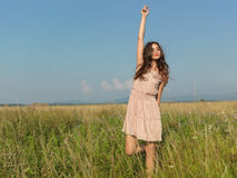 Happy, young woman standing in green field Stock Photography