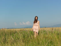 Happy, young woman standing in green field Royalty Free Stock Photo