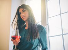 Happy young woman standing in her apartment drinking a glass of red wine next the window with a cute smile royalty free stock photos