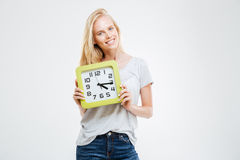 Happy young woman standing and holding wall clock Stock Images