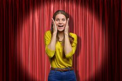 Happy young woman standing and looking at camera with hands on face, in spotlight, against red stage curtain. stock images