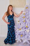 Happy young woman standing near the Christmas tree Royalty Free Stock Photography