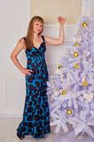 Happy young woman standing near the Christmas tree Stock Image