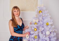 Happy young woman standing near the Christmas tree Royalty Free Stock Images