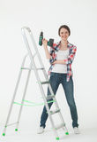 Happy young woman standing near the stepladder and holding a scr Stock Photo