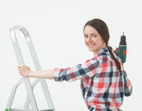 Happy young woman standing near the stepladder and holding a scr Royalty Free Stock Images