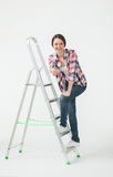 Happy young woman standing near the stepladder and showing thumb Royalty Free Stock Photo