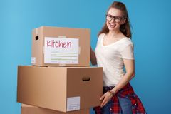 Happy young woman standing next to cardboard boxes on blue Royalty Free Stock Photography