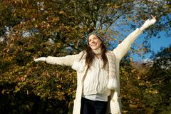 Happy young woman standing outdoors with arms outstretched Stock Photos