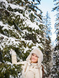 Happy young woman standing outdoors near snowy spruce branch Royalty Free Stock Image
