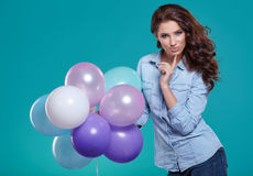 Happy young woman standing over blue wall and holding balloons. Stock Photo