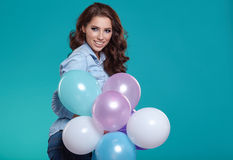 Happy young woman standing over blue wall and holding balloons. Royalty Free Stock Photography