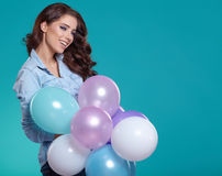 Happy young woman standing over blue wall and holding balloons. Stock Images