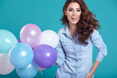 Happy young woman standing over blue wall and holding balloons. Royalty Free Stock Photos