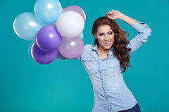 Happy young woman standing over blue wall and holding balloons. Stock Photos