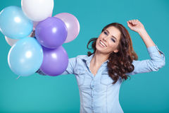 Happy young woman standing over blue wall and holding balloons. Royalty Free Stock Images