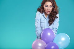Happy young woman standing over blue wall and holding balloons. Royalty Free Stock Image