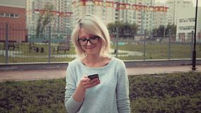 Happy young woman standing in the park area among buldings using her smartphone texting stock video