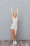 Happy young woman standing and pointing up with both hands. Happy chaming young woman standing and pointing up with both hands over gray background Stock Photos