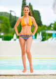 Happy young woman standing at poolside Stock Photography