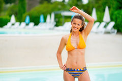Happy young woman standing at poolside Stock Images