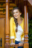 Happy young woman standing on the porch of a wooden house Stock Photography