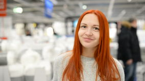Happy young woman is standing in a shopping mall stock video footage